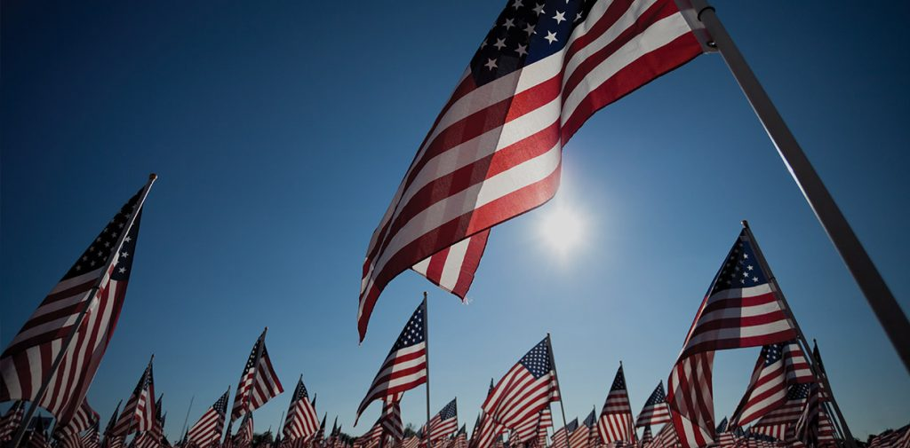 Field of American flags with a blue sky.