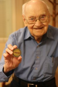 George Strauch shows off the military challenge coin gifted to him by the VSC.