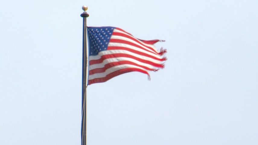 Worn American flag blowing in the wind from a flag pole.