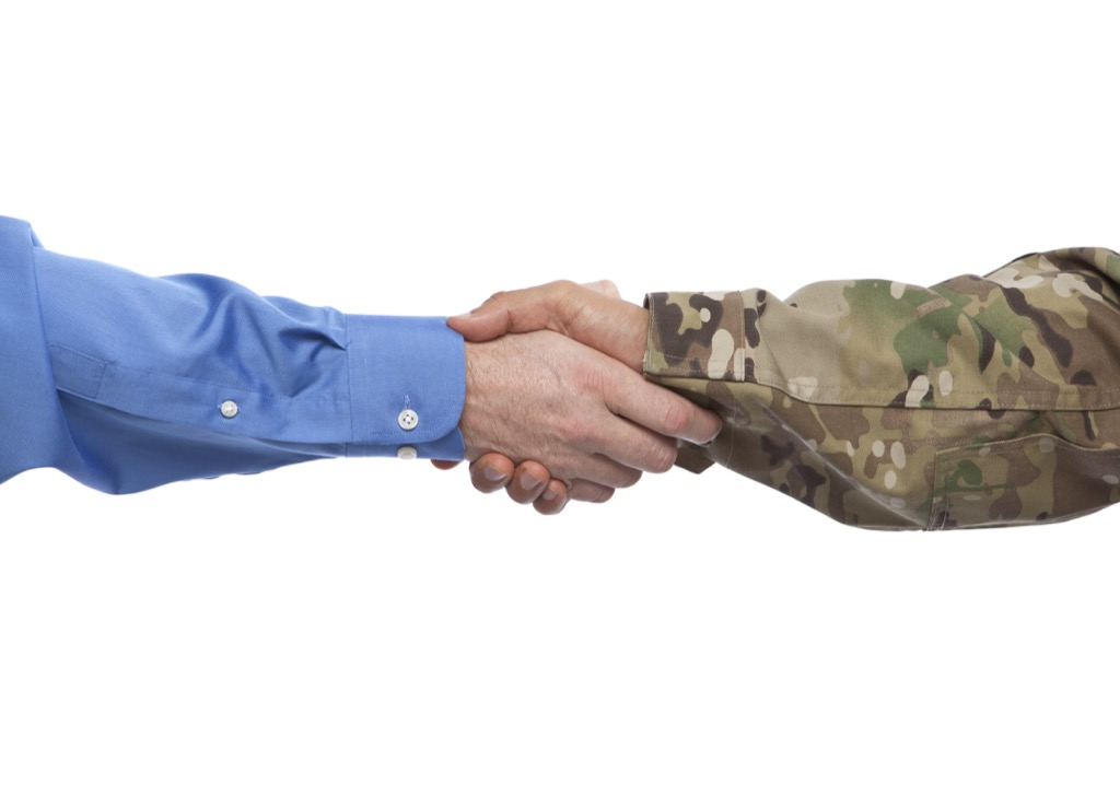 Soldier and businessman shaking hands