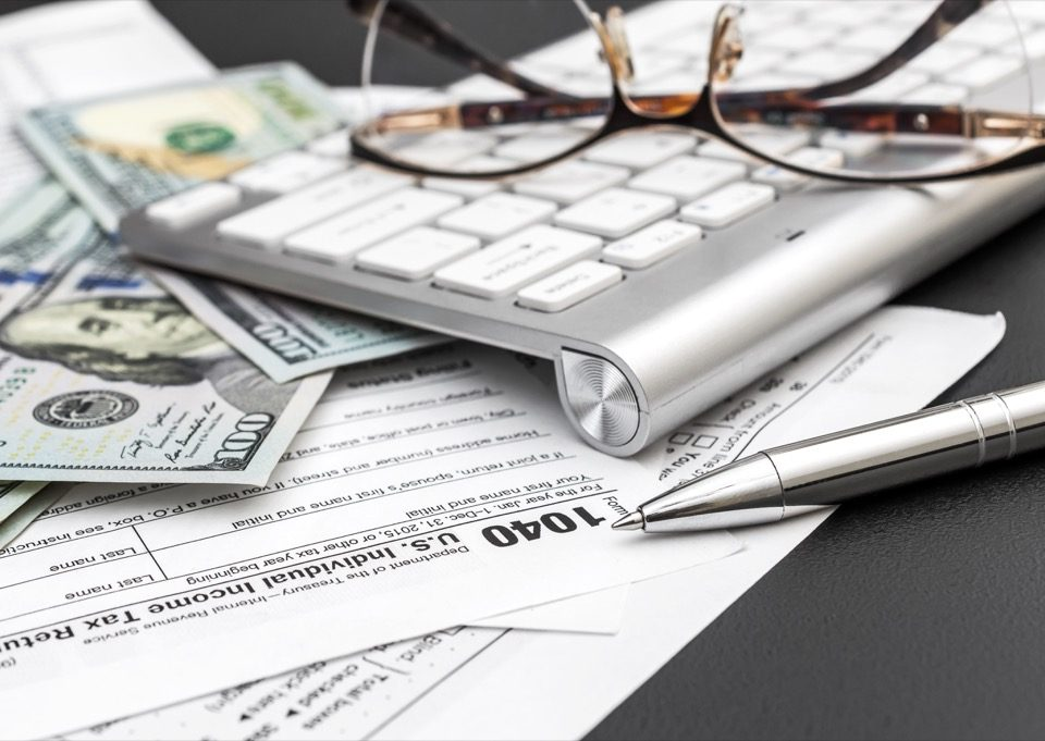 Money, a keyboard, and tax forms
